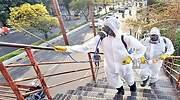 Unos trabajadores suben las escaleras de un inmueble para desinfectarlo