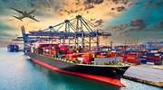 Un barco cargado de mercancas en el puerto con un avin al fondo