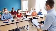 Un profesor da clase en un aula donde todos llevan mascarillas