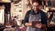 El propietario de una tienda de ropa y regalos usa una tablet