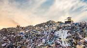 Una excavadora trabaja sobre un montn de residuos de un vertedero