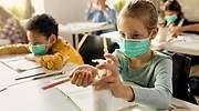 Nina-en-clase-con-gel-desinfectante-y-mascarilla-iStock.jpg