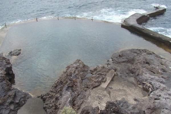 Una ola arrastra a tres personas en una piscina natural en for Piscina natural puerto santiago