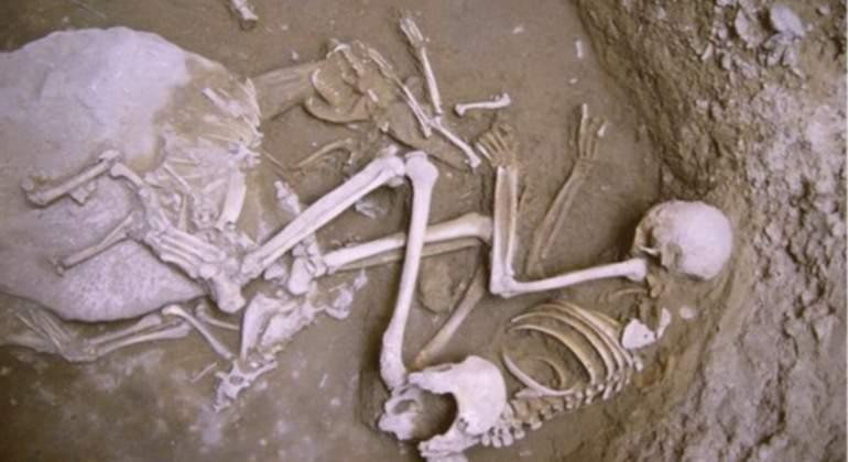 Esqueleto humano abrazado a restos óseos de un zorro.