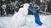 Una-nina-vestida-de-azul-con-un-muneco-de-nieve-iStock.jpg
